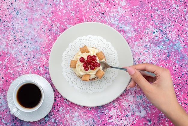 Vista superior de la torta con crema dentro de la placa con una taza de café en el fondo de color pastel de color galleta para hornear