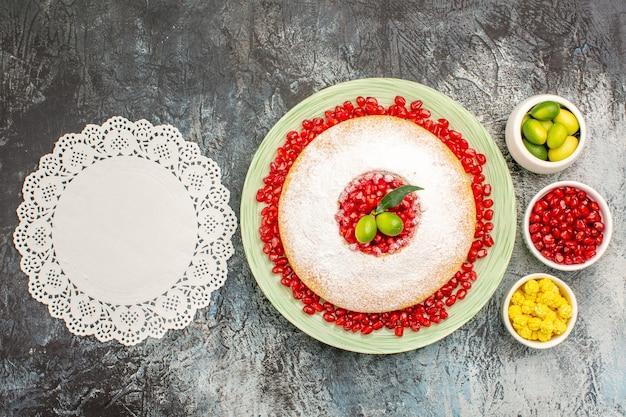 Vista superior de la torta y dulces un plato de torta con granada, frutas cítricas, dulces, tapete de encaje