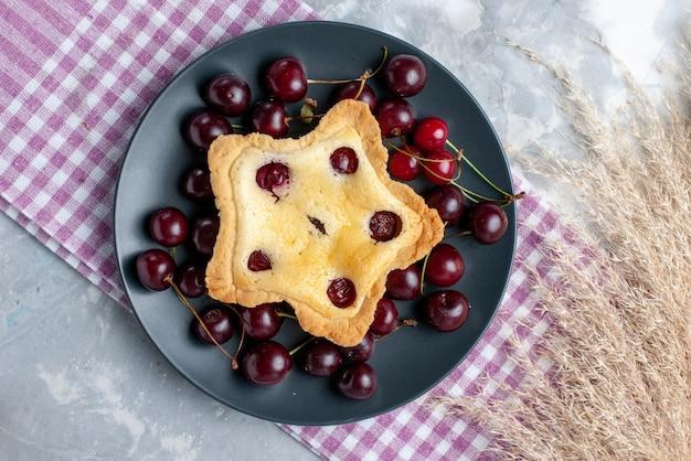 Vista superior de la torta en forma de estrella con guindas frescas dentro de la meseta en la mesa de luz pastel de frutas hornear pastel color cereza