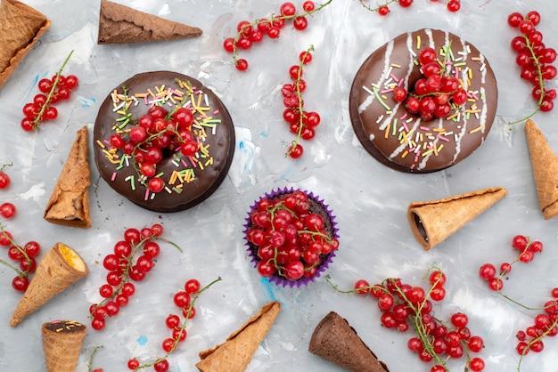 Una vista superior de tortas de chocolate con rosquillas diseñadas con frutas y cuernos sobre el fondo blanco pastel de galletas donut azúcar