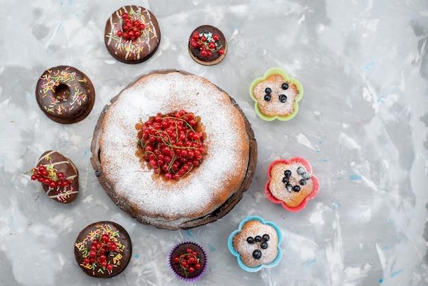 Una vista superior de tortas de chocolate con rosquillas diseñadas con frutas y grandes tartas redondas sobre el fondo blanco pastel biscuit donut chocolate