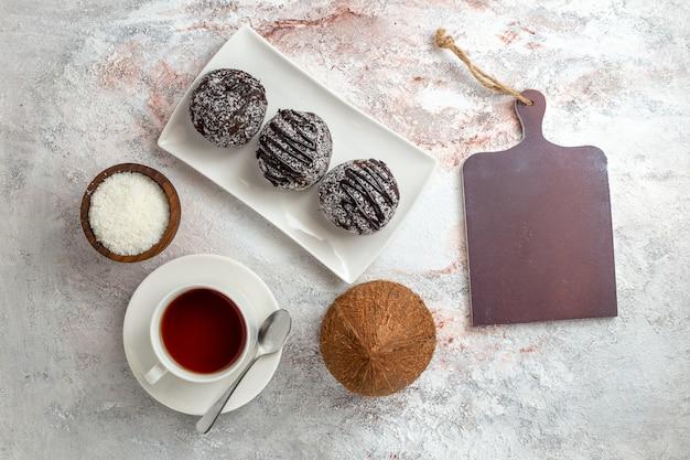 Vista superior de tortas de chocolate con taza de té sobre fondo blanco galleta de pastel de chocolate galleta dulce de azúcar
