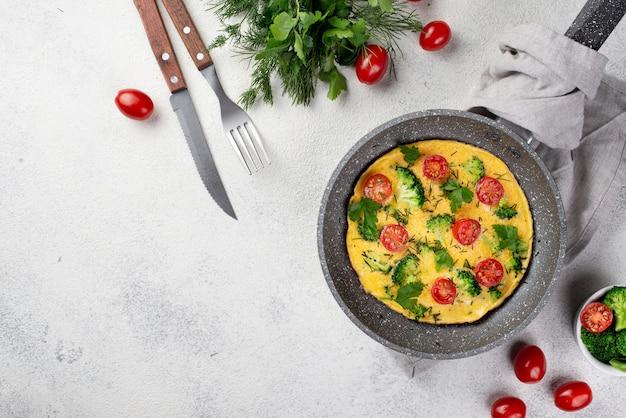 Vista superior de la tortilla de desayuno en sartén con tomates y copia espacio