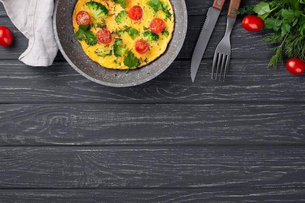 Vista superior de tortilla para el desayuno con tomates y cubiertos.