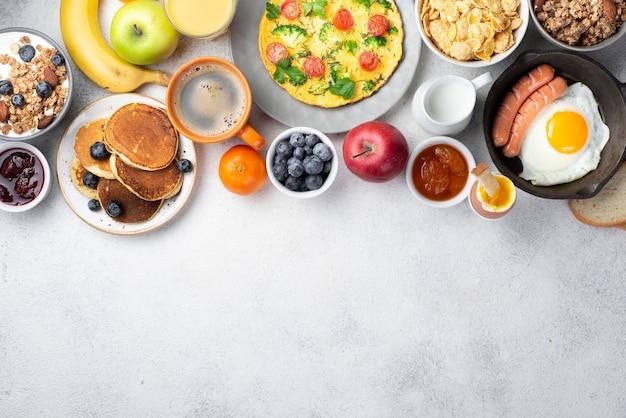 Vista superior de tortilla con huevo y salchichas y variedad de alimentos para el desayuno.