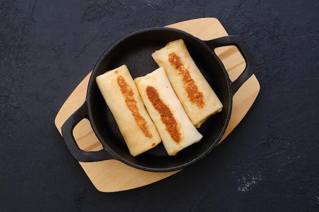 Vista superior de tortitas finas rellenas de carne de pavo en una sartén de hierro fundido