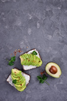 Vista superior de tostadas de aguacate para el desayuno con hierbas y espacio de copia