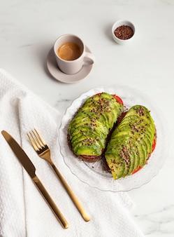 Vista superior de tostadas de aguacate en plato con cubiertos y café