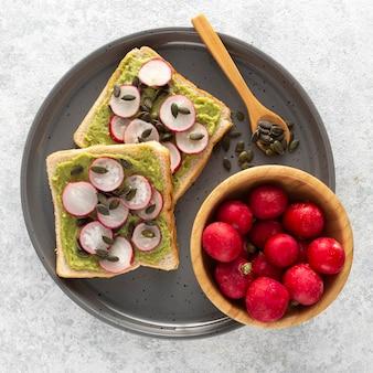 Vista superior de tostadas de aguacate con rábano y semillas en bandeja
