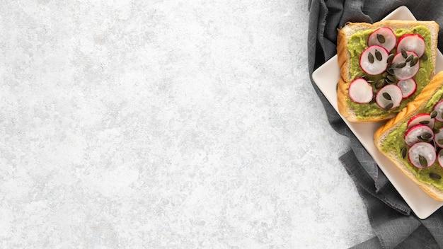 Vista superior de tostadas de aguacate con rábano y semillas en un plato con espacio de copia