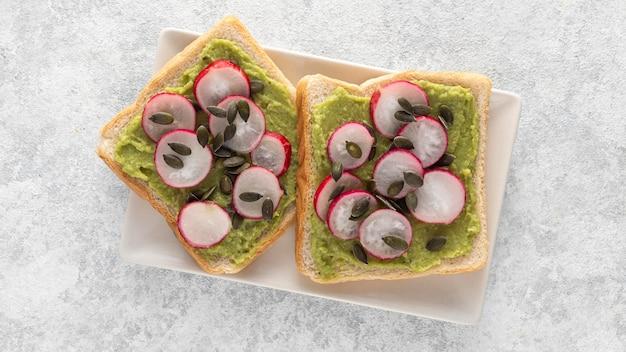Vista superior de tostadas de aguacate con rábano y semillas en un plato