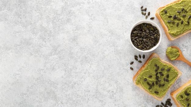 Vista superior de tostadas de aguacate con semillas y espacio de copia