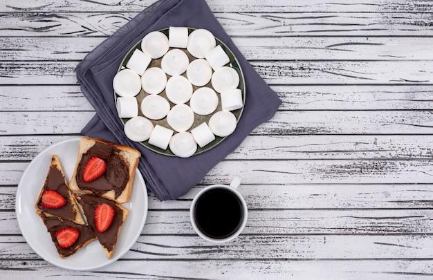 Vista superior de tostadas de desayuno con chocolate y fresa, malvavisco y café en superficie de madera blanca horizontal