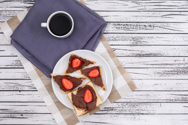Vista superior de tostadas de desayuno con chocolate y fresa en plato y café en superficie de madera blanca horizontal