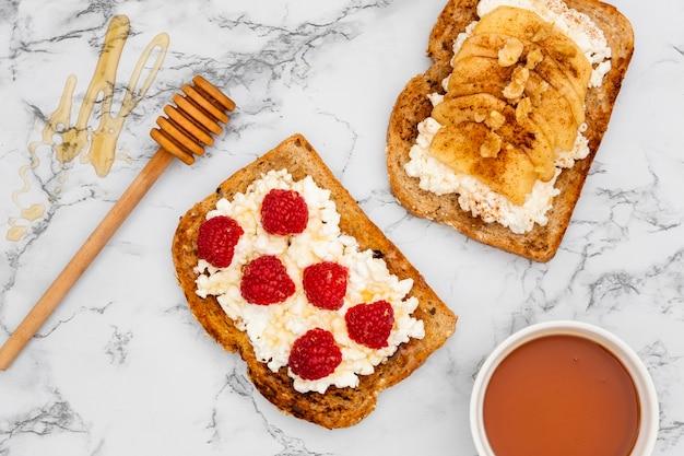Vista superior de tostadas con frambuesas y cucharón de miel