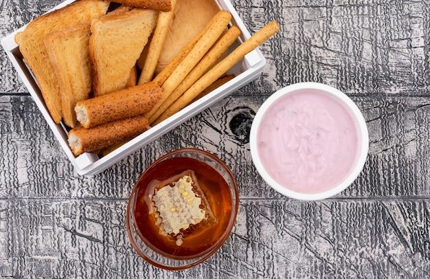Vista superior de tostadas con galletas en caja con miel y yogurt en superficie blanca horizontal