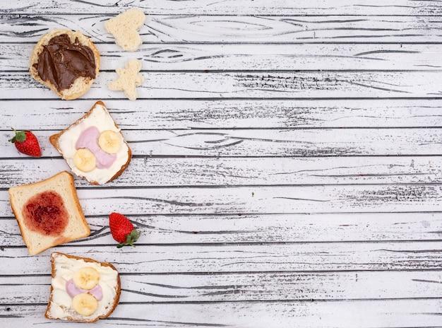 Vista superior de tostadas con mermelada, yogur y copia espacio sobre fondo blanco de madera horizontal