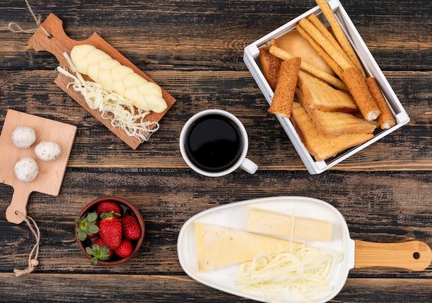 Vista superior de tostadas con queso y café en superficie de madera oscura horizontal