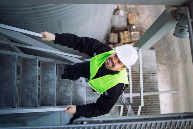Vista superior del trabajador de la fábrica subiendo escaleras metálicas en la construcción de silos industriales