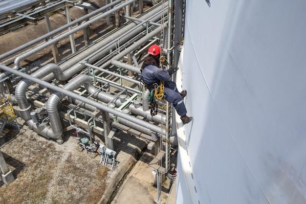Vista superior trabajador masculino inspección de acceso por cuerda de plomería industria de tanques de almacenamiento debajo de oleoducto