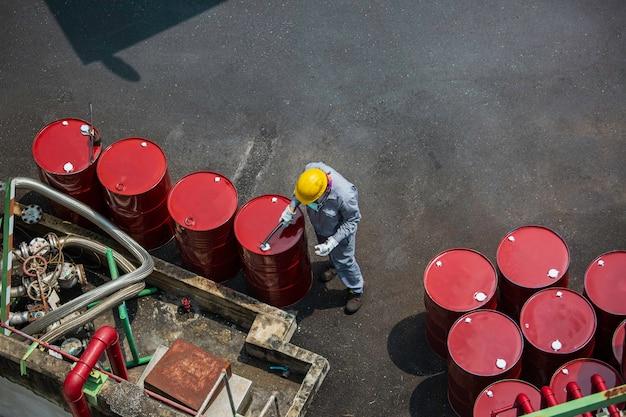 Vista superior trabajador masculino registro de inspección tambor aceite stock barriles rojo vertical o químico para la industria.