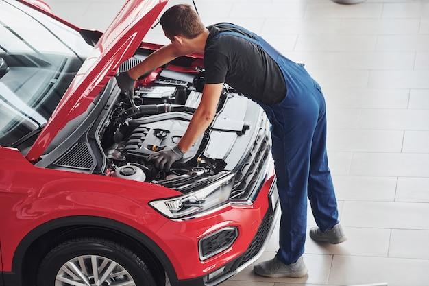 Vista superior del trabajador masculino en uniforme que repara automóvil rojo
