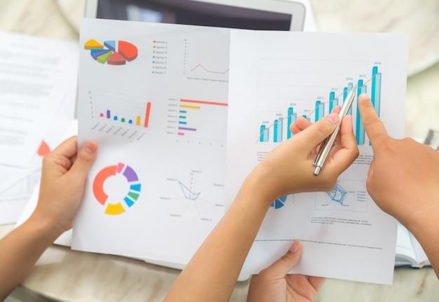 Vista superior de trabajadores comprobando documentos estadísticos