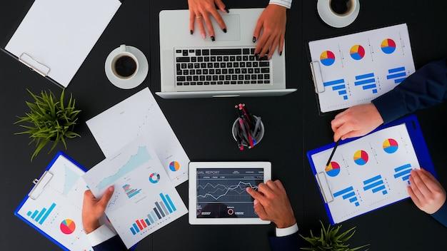 Vista superior de trabajadores de oficina discutiendo diagramas financieros comerciales y trabajando en dispositivos digitales