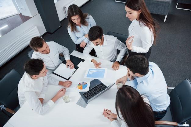 Vista superior de los trabajadores de oficina en ropa clásica sentados cerca de la mesa usando una computadora portátil y documentos