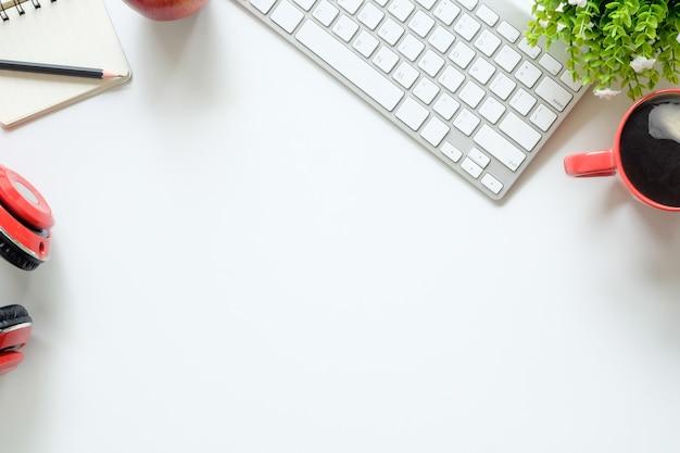 Vista superior de trabajo de escritorio computadora, teléfono de la cabeza, lápiz, papel de bloc de notas y taza de café en el área de trabajo.