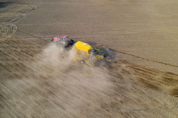Vista superior del tractor de siembra de semillas de maíz en el campo, fotografía de drone con vista de ángulo alto