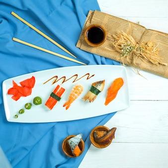 Vista superior del tradicional nigiri japonés sushi con atún salmón anguila y camarones en azul y blanco