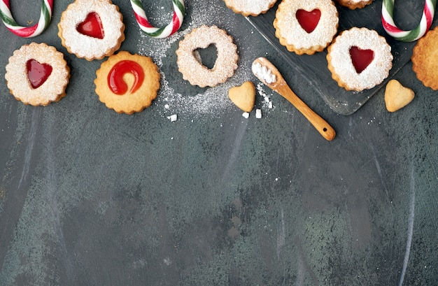 Vista superior de las tradicionales galletas linzer de navidad con mermelada de fresa en bandeja de madera sobre fondo oscuro, copyspace