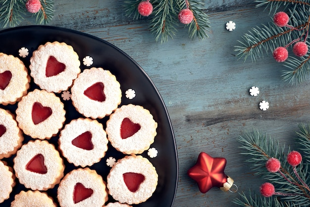 Vista superior de las tradicionales galletas linzer de navidad con mermelada roja sobre madera rústica decorada con bayas srars y copos de nieve