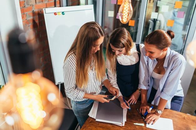 Vista superior de tres alegres alumnas mirando la pantalla del teléfono móvil de pie en el aula