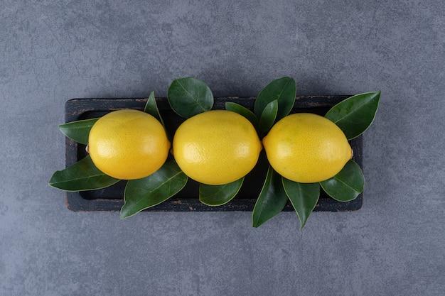 Vista superior de tres limón fresco con hojas sobre fondo gris.