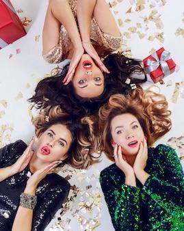 Vista superior de tres mujer sorprendida tirada en el suelo, celebrando el año nuevo o la fiesta de cumpleaños. usar vestido de lentejuelas de lujo y joyas. confeti dorado brillante, cajas de regalo rojas.
