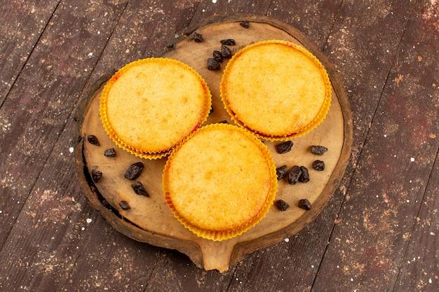 Vista superior de tres pasteles redondos deliciosos dulces en el escritorio marrón y fondo de madera