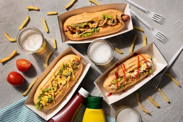 Vista superior de tres perros calientes con salsa de tomate y mostaza