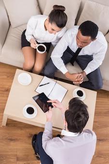 Vista superior de tres personas de negocios están sentados en la mesa.