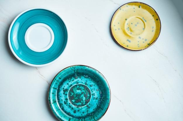 Vista superior en tres placa de cerámica vacía hecha a mano sobre una superficie de mármol gris. copiar espacio para texto. utensilios de cocina con estilo