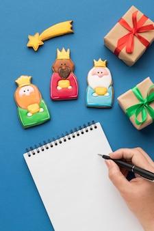Vista superior de tres reyes con estrella fugaz y escritura a mano en el cuaderno
