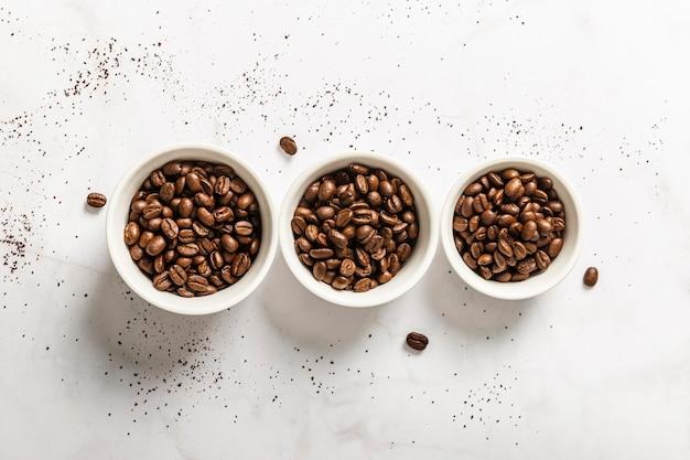 Vista superior de tres tazas con granos de café tostados