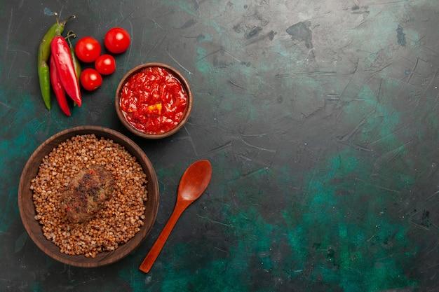 Vista superior de trigo sarraceno cocido con chuleta y salsa de tomate sobre superficie verde