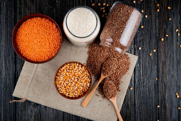 Vista superior de trigo sarraceno se esparce de una lata con lentejas de maíz y arroz sobre arpillera