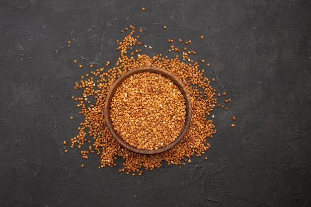Vista superior de trigo sarraceno fresco crudo dentro de la placa en el espacio oscuro