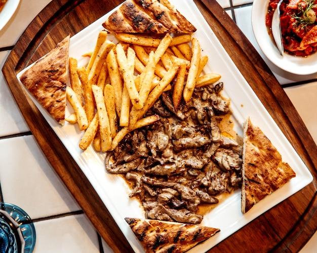 Vista superior de trozos de carne a la parrilla servidos con papas fritas y pan tostado tandoor