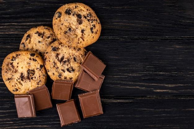 Vista superior de trozos de chocolate con leche y galletas de avena sobre fondo rústico oscuro