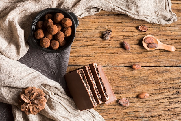 Vista superior trufas de chocolate en tazón y barra de chocolate