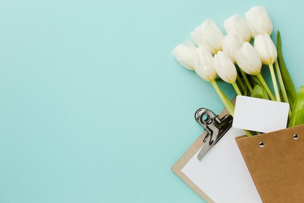 Vista superior tulipán flores blancas y bloc de notas con espacio de copia
